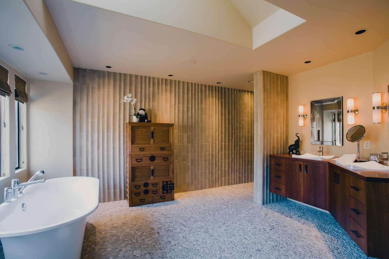 master bath, pebble tile floor, spa tub, tile walls, walkin shower, floating cabinet, wood counter